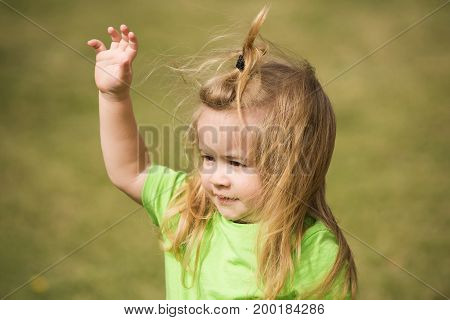 Boy small kid with smiling cute face blond long hair in green shirt waving with his hand on natural grass background