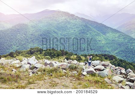 Breathtaking mountain landscape with hiker woman standing on the rocks and enjoying beautiful view