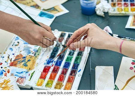 Hands of young girls taking the paints out with paintbrushes from the set of paints