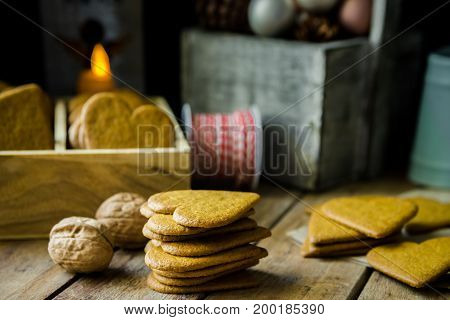 Pile of home baked Christmas gingerbread cookies in wood box burning candle red and white ribbon pine cones and colorful baubles rustic kitchen interior festive atmosphere