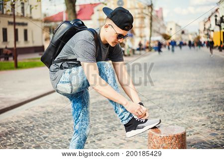 Hipster style guy. handsome guy with glasses and a fashionable hairdo. vintage photo. The guy standing near the old wooden wall. In the hands of a fashion backpack and a lion, sunglasses