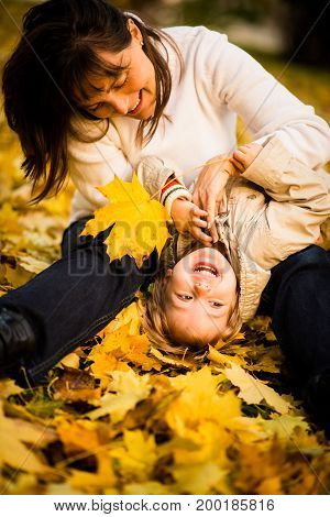 Mother and child having great fun together in autumn nature - girl is upside down