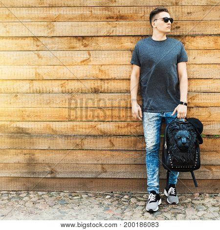 Hipster style guy. handsome guy with a fashionable hairdo. vintage photo. The guy standing near the old wooden wall. In the hands of a fashion backpack and a lion, sunglasses, sneakers, jeans