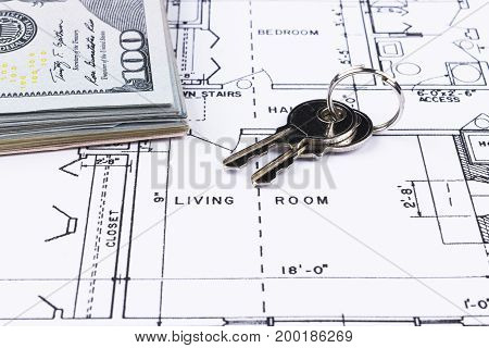 Stack of money with key lying on construction drawing of house blueprint house plan concept money for new real estate. blueprint and drawing instruments on the worktable.