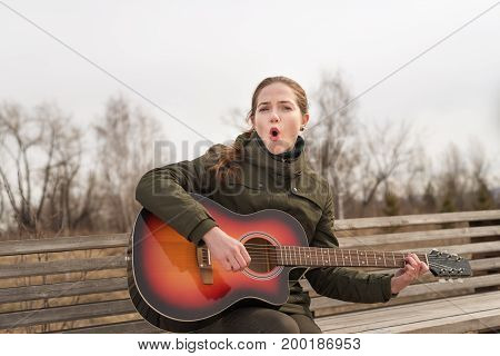 Smiling woman playing the guitar and singing on a wooden bench outdoors