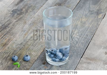 Blueberry flavored water on rustic wooden background. Diet Detox Clean Eating.