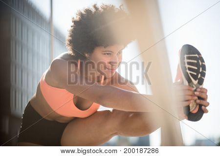 Smiling fit woman relaxing her leg muscles