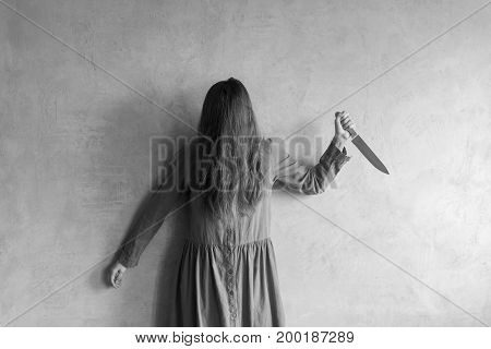 Furious woman with a knife. Her face is covered with hair. Retouched image.