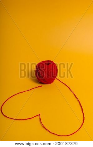 Red yarn with heart symbol on yellow background.