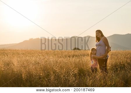 Smiling young pregnant woman holding her daughter close to belly