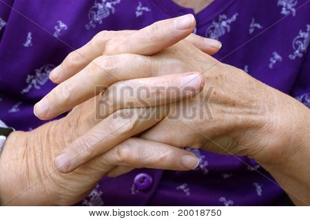 Praying Hands Of An Older Person With A Dark Blue Sweater