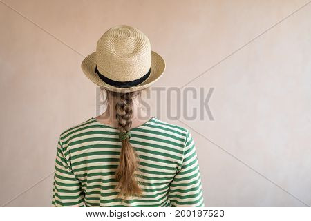 Young woman in a sailor's striped vest and a straw hat standing with her back to the viewer. Picture taken with a natural light.