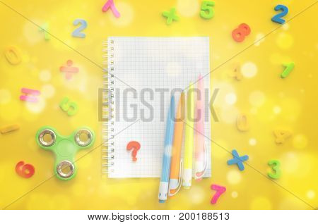 Notebook with with multi-colored numerals calculator and hand spinner on yellow background. Overhead food shots. Copy-space composition. Back to school concept. Bokeh effect