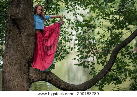 Caucasian woman standing in yoga balance Utthita Hasta Padangusthasana pose. She hold trank of tree. Unity of man with nature
