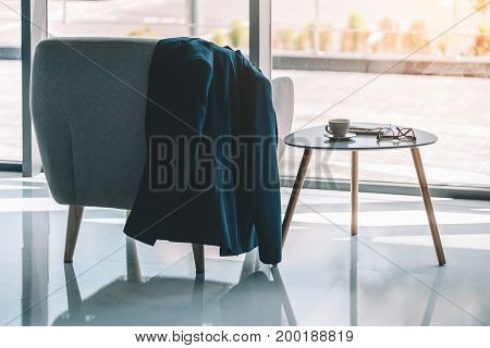 businessmans jacket hanging on armchair in lobby with coffee and supplies on table