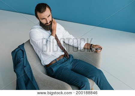 view of concentrated young businessman sitting in armchair