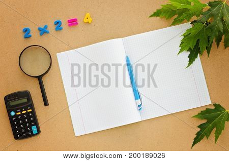 School Desk with notebook pen calculator magnifier and numbers. Back to school concept. Top view flat lay overhead. Copy space background