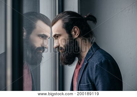 Man Looking At Reflection In Glass
