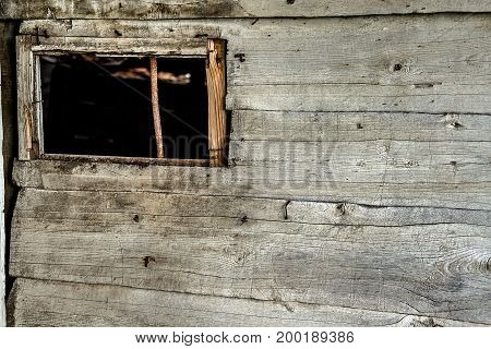 Old weathered wooden barn wall with window