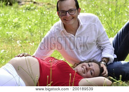 Pregnant woman couple lying down on grass