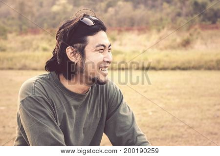 close up face of younger asian man laughing happiness emotion