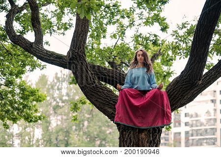 Beautiful young girl meditating in autumn park on green oak tree
