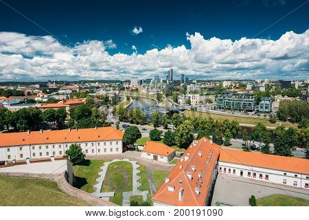 Vilnius, Lithuania. Modern City And Part Of Old Town Under Dramatic Sky In Summer Day. Behind New Arsenal At Northern Foot Of Castle Hill, One Can Spot Foundation Of Church Of St. Ann And St. Barbara