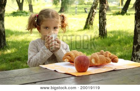 young girl drink milk in park