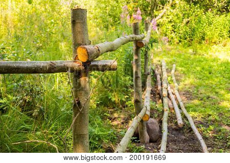 The fence is handmade from trees. The rural design of the fence site. Fence for the cattle in the village.