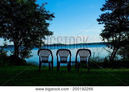 Three vacant places available, empty chairs by a lake