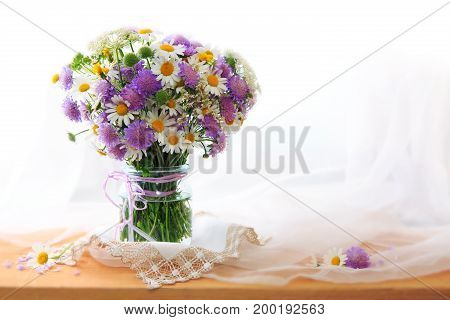A bouquet of white chamomile in a glass vase on a wooden background and a white chiffon fabric. Birthday card.