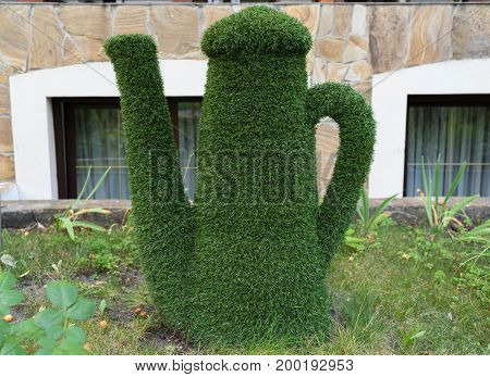 Figure Of Kettle Made Of Green Lawn Grass In The Park, Free Space. Green Grass Covered Topiary Kettl