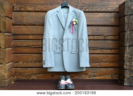 Stylish Elegant Wedding Groom Suit With Buttonhole Hanging On Wooden Background. Gray Suit Hangs Abo