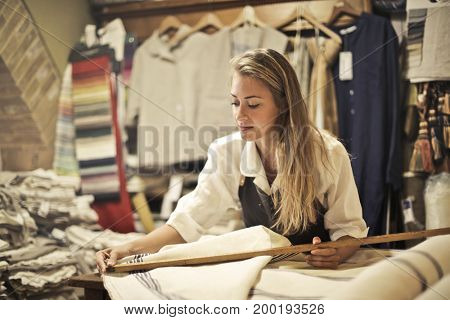 Dressmaker in her boutique measuring a piece of fabric
