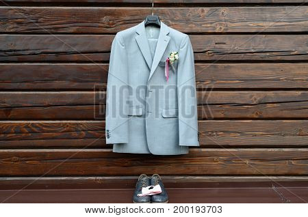 Stylish Elegant Wedding Groom Suit With Buttonhole Hanging On Wooden Background With Copy Space. Gra