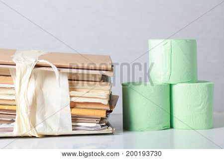 A Stack Of Waste Paper And A Roll Of Toilet Paper