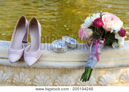Fresh wedding bouquet box with rings and beige bride's shoes stand on stone fountain outdoor closeup free space. Wedding details with copy space. Wedding morning preparation