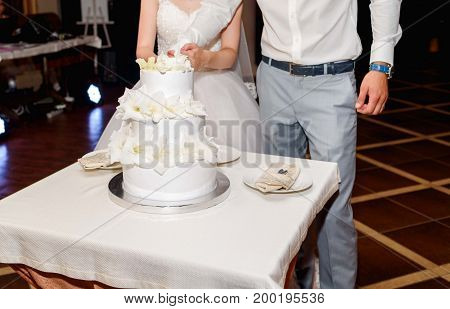 Stylish Bride And Groom Cutting White Multi Level Wedding Cake With Fresh Flowers In The Restaurant