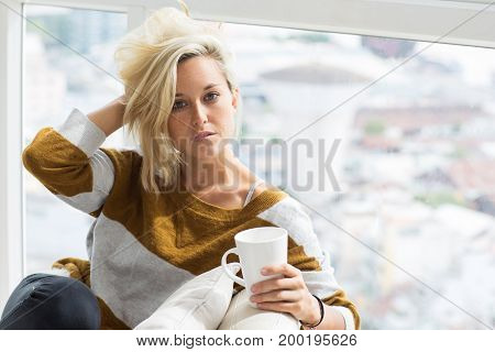 Portrait of serious young Caucasian woman wearing sweater sitting holding cup of tea, tousling hair and looking at camera