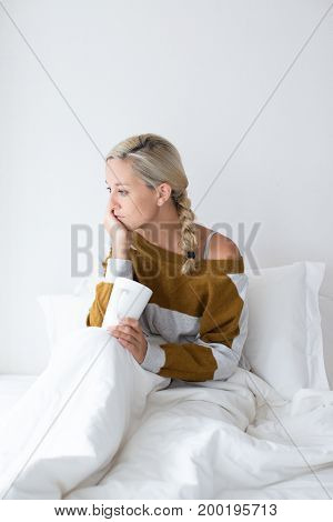Portrait of upset young Caucasian woman wearing sweater sitting on bed under blanket and drinking tea