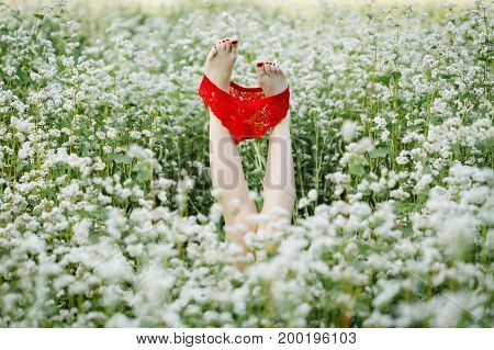 Close-up Female legs with red panties on a white field .