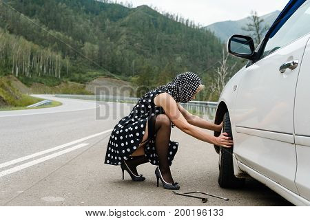 Pin-up Woman Changing Car Tire On Road.