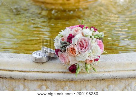 Close Up Of Beautiful Fresh Wedding Bouquet Of Pink And White Roses Near Two Golden Wedding Rings In