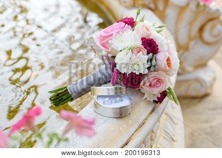 Close Up Of Beautiful Fresh Wedding Bouquet Of Pink And White Roses And Two Golden Wedding Rings In