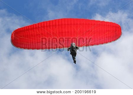 Paraglider flying his wing in a blue sky