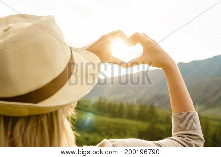 Woman making heart-shape with hands outdoors. Heart.