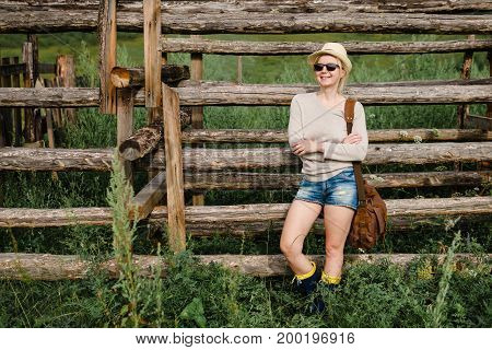 Woman In Casual Clothes Standing By A Wooden Fence.