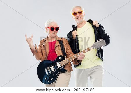 music, age and people concept - happy senior couple in sunglasses with electric guitar showing rock hand sign