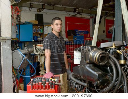 a portrait of a young mechanic in his workshop