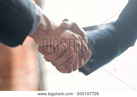 Business people shaking hands finishing up meeting. Successful businessmen handshaking after good deal.